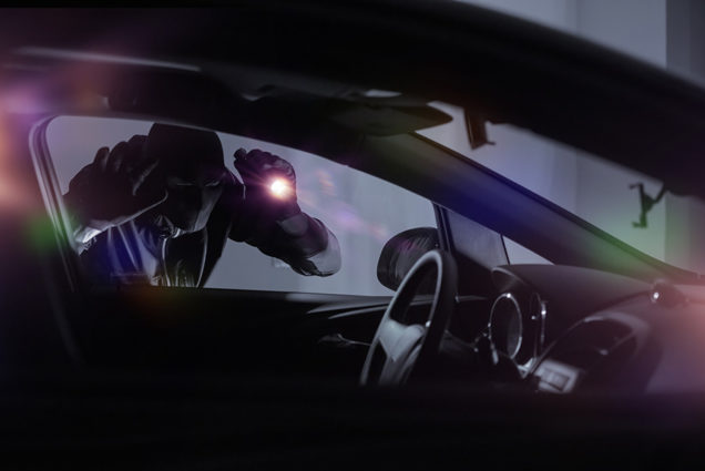 Car Robber with Flashlight Looking Inside the Car. Car Security Theme.